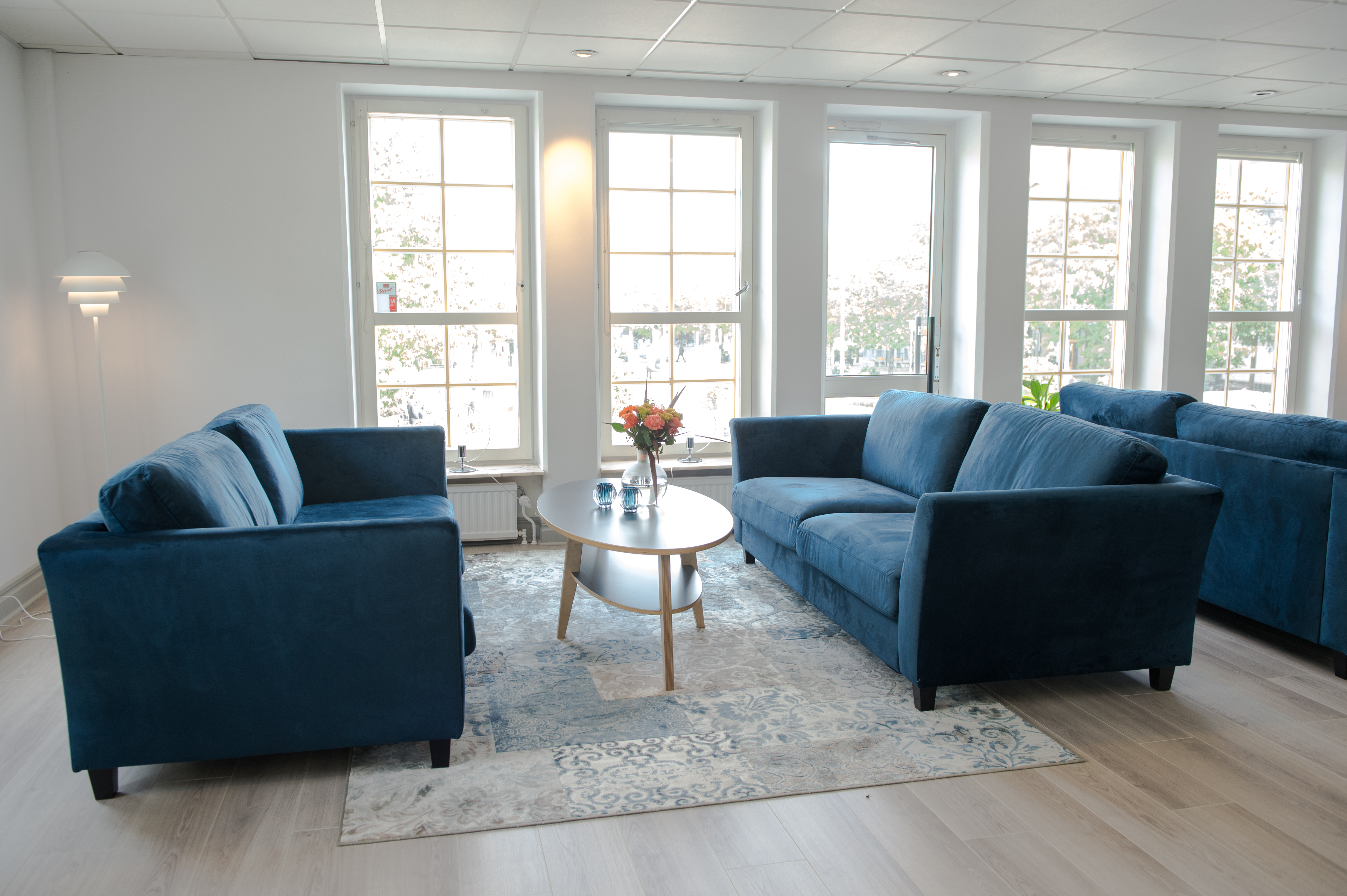 En soffgrupp i blått med fönster i bakgrunden
